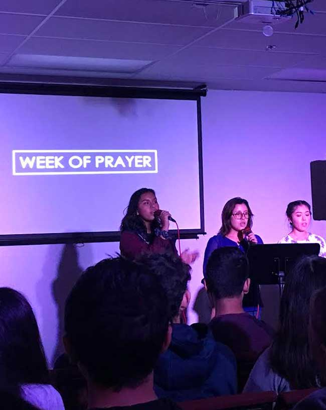Students on stage leading a week of prayer program