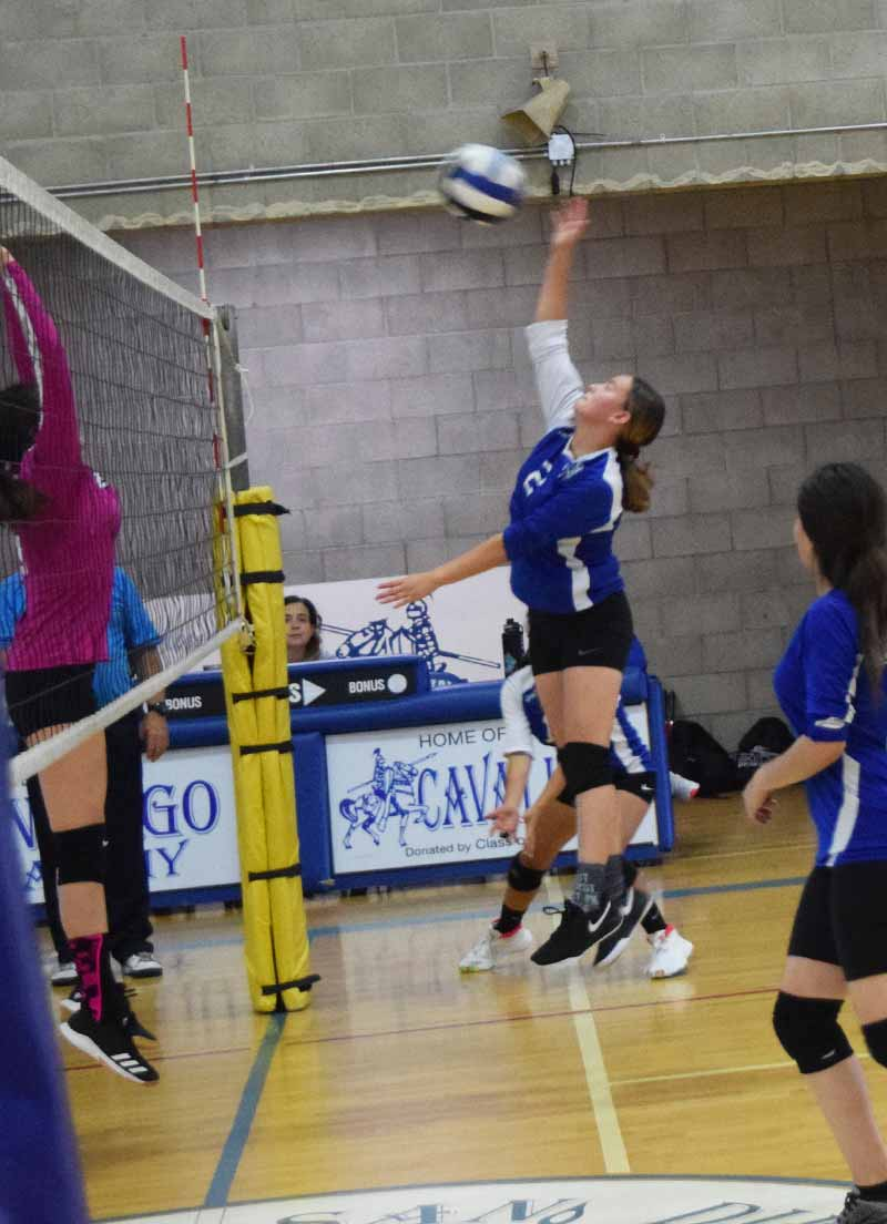 Player on the girls volleyball team spiking the ball