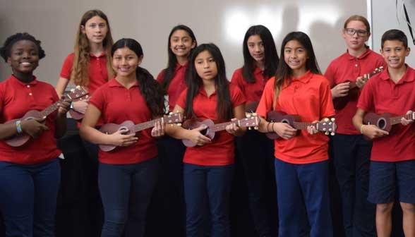 6th graders holding ukuleles