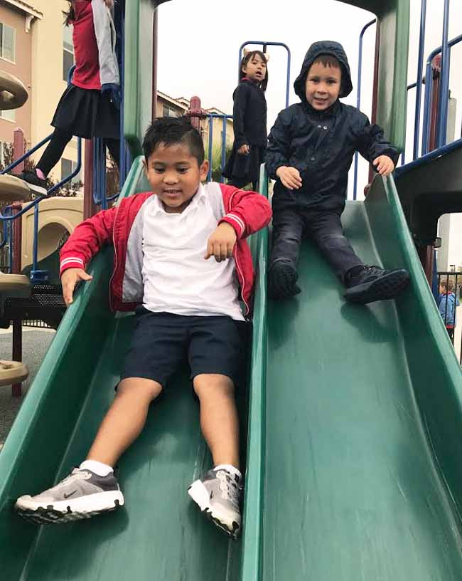Young students going down a slide