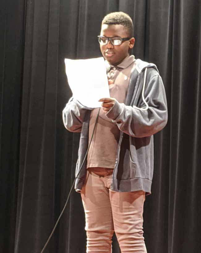 Junior high student reading on stage