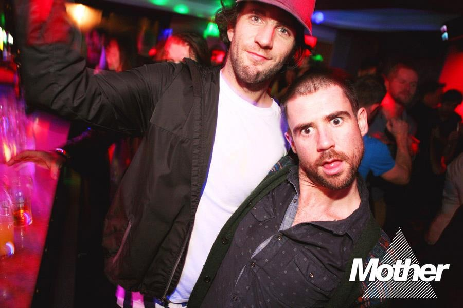 Two men posing for a photo in a club, behind them a crowd can be seen dancing.The Mother logo can be seen on the lower right part of the photo.
