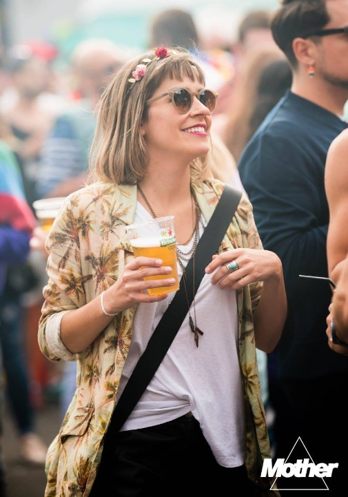 A girl wearing sunglasses and holding a pint at a festival. The Mother logo can be seen on the lower right part of the photo.