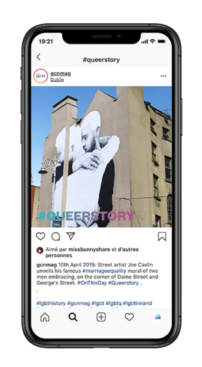 iPhone screen displaying a post from GCN's Instagram account. The post is a photo of Joe Caslin Marriage Equality mural art of two men hugging each other. The #queerstory logo is running across the photo.