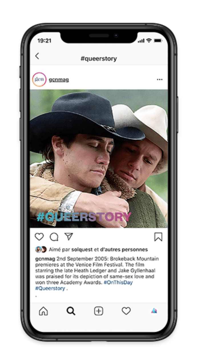 "iPhone screen displaying a post from GCN's Instagram account. The post is a still from ""Brokeback Mountain"" of actors Jake Gyllenhaal and Heath Ledger hugging. The #queerstory logo is running across the photo."