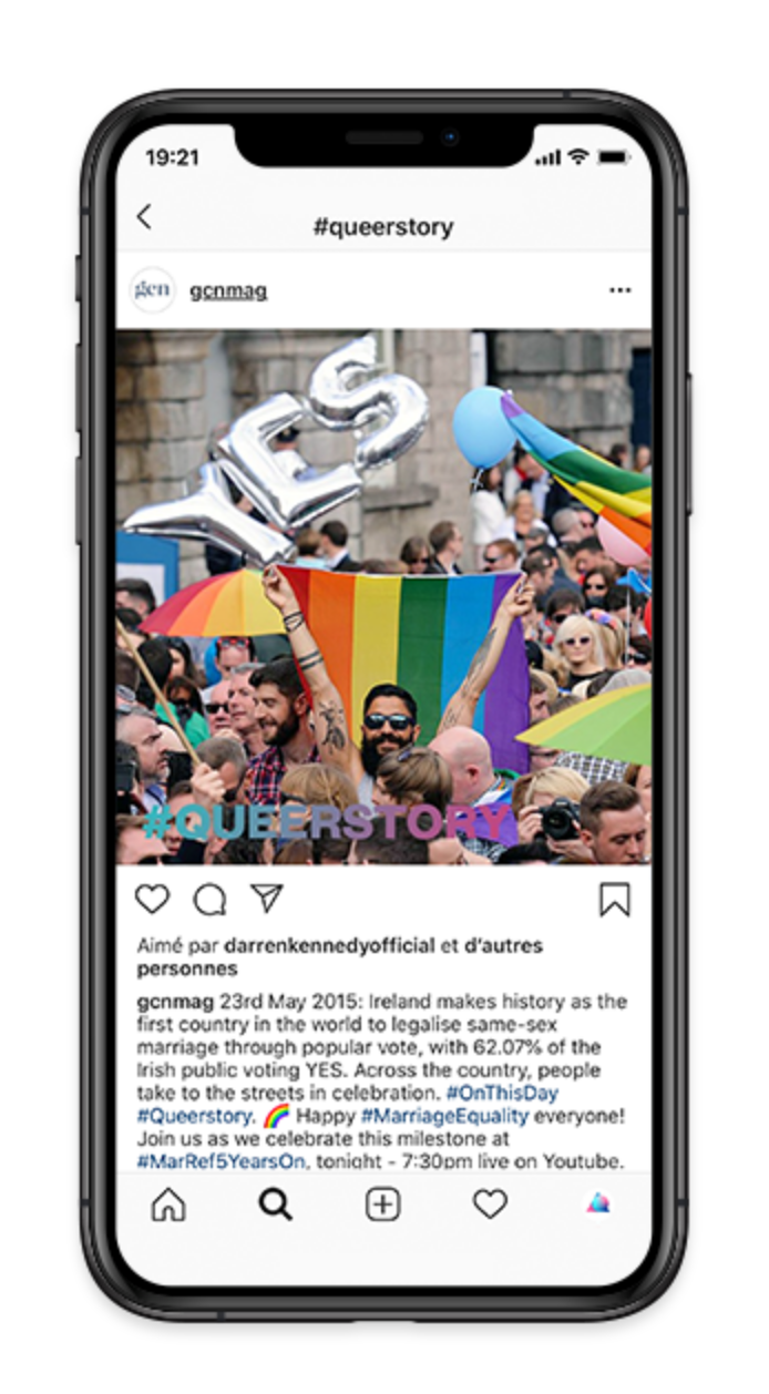 "iPhone screen displaying a post from GCN's Instagram account. The post is a photo of a crowd of people waving rainbow flags and a balloon that reads ""yes"". The #queerstory logo is running across the photo."