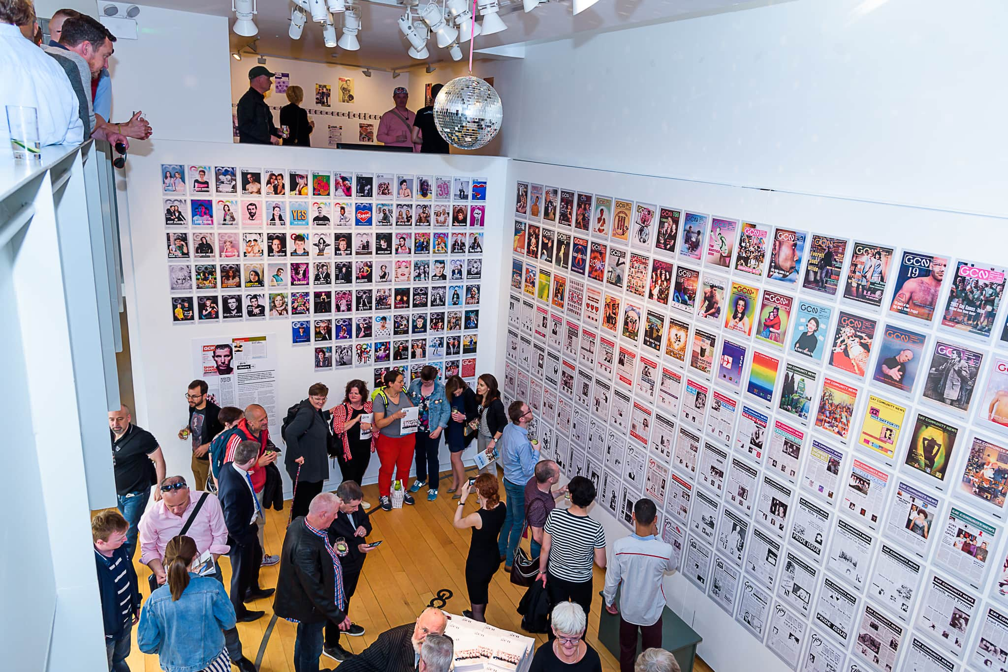 A photo of a crowd of people looking at walls covered in GCN magazine covers at the Proof exhibition, which shares some of the source material with GCN's Prism.