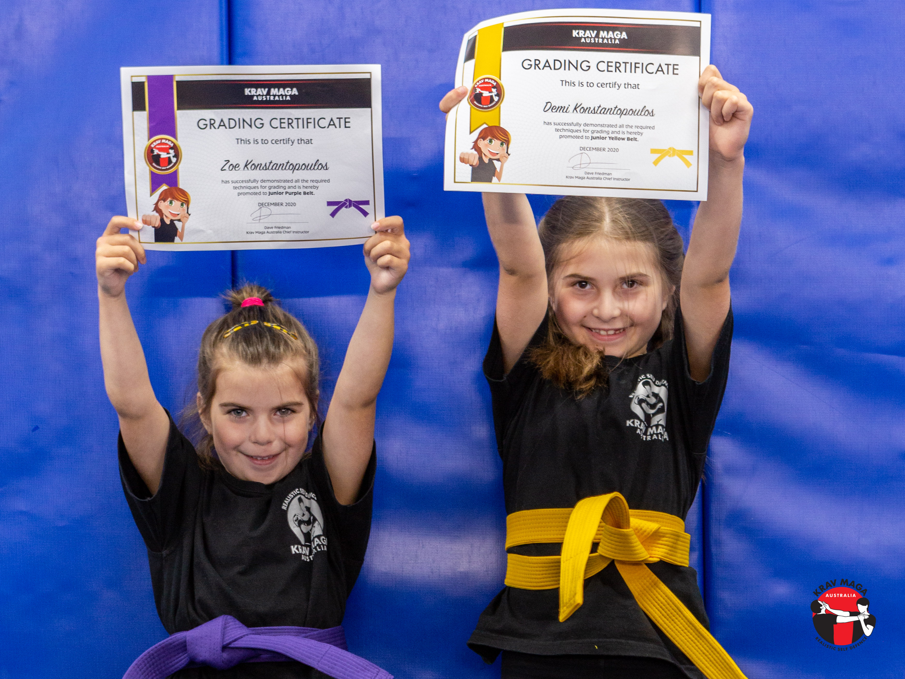 Two krav maga students holding up their grading certificate after class