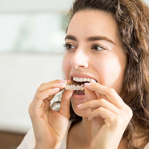 Woman fitting Invisalign aligners