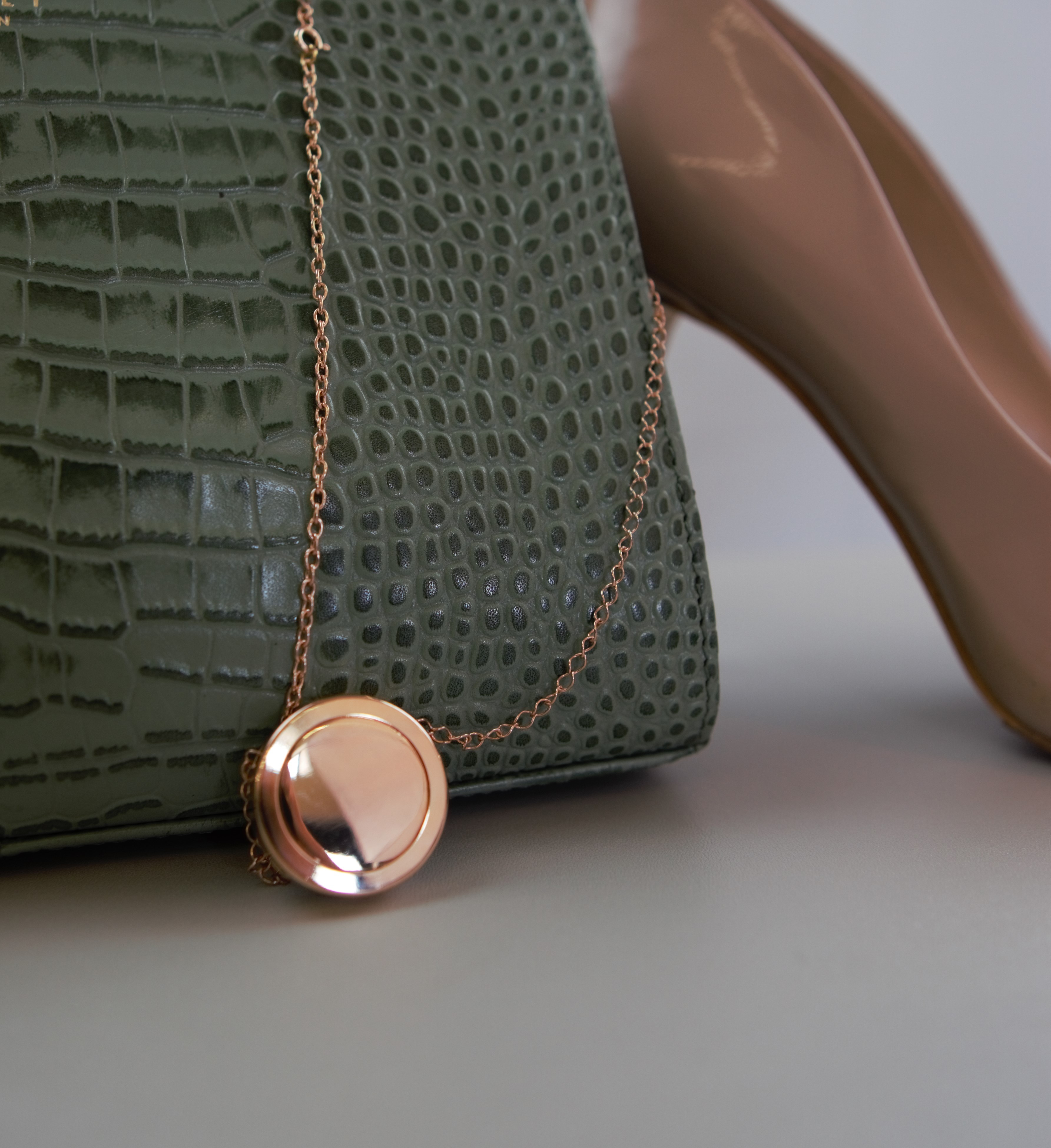 noti safety necklace in styled photo with bag and shoe