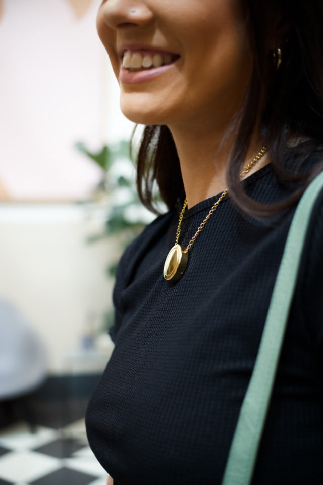 woman wearing smart safety necklace gold