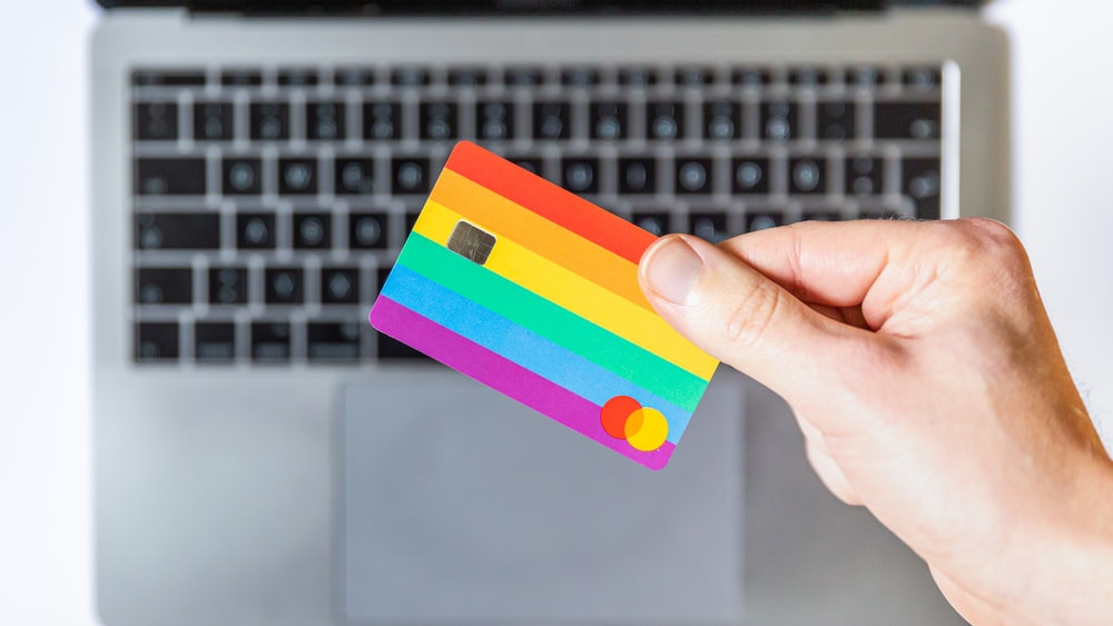 person holding yellow and pink payment card