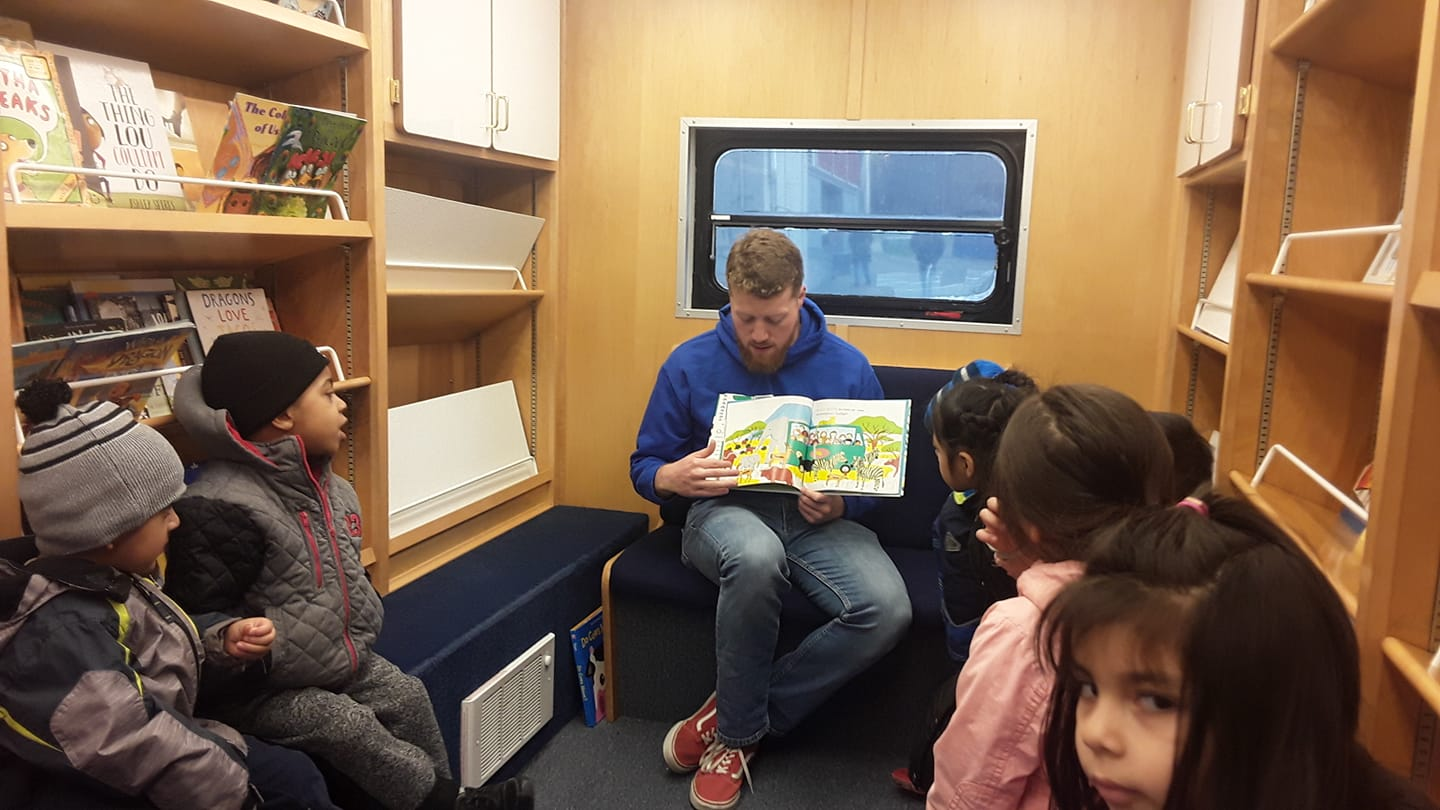 Students listen to a story on the storymobile