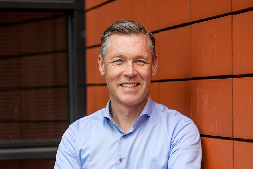 Hans Broekhuizen, burgemeester van Twenterand leunend tegen het Gemeentehuis