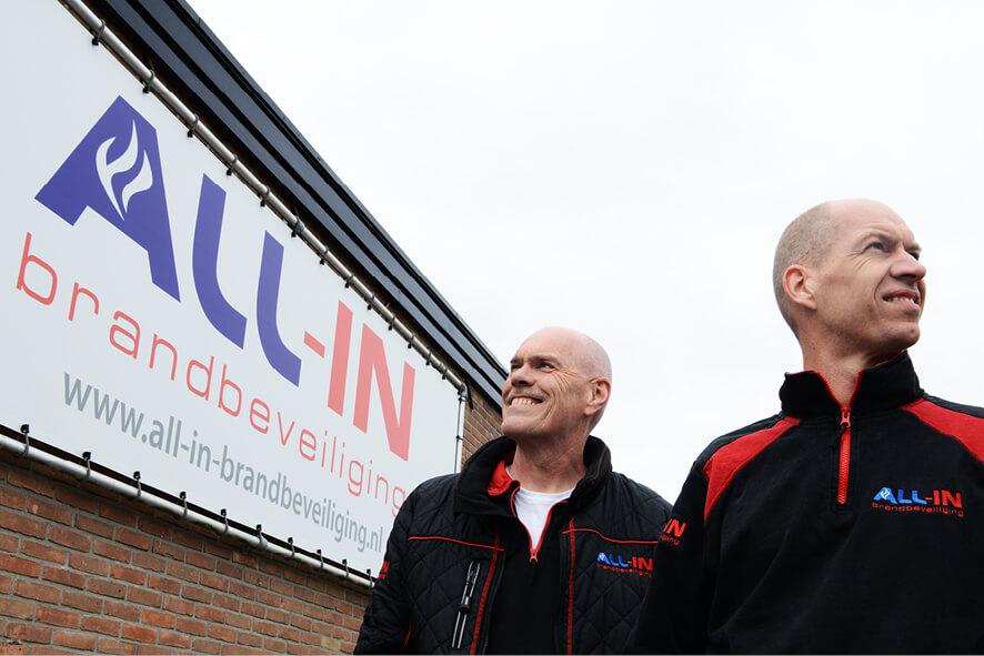 Erik Hoeks en Lourens Bouwmeester bij het logo van het bedrijf All-in Brandbeveiliging