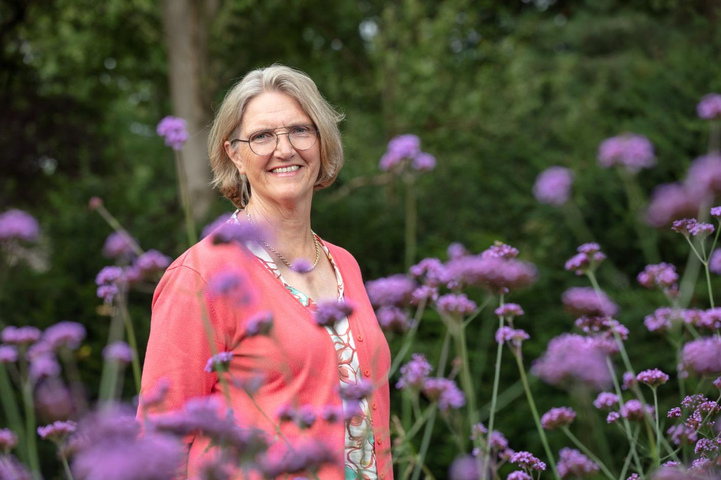 Nelly Remmerswaal, de oprichter van stichting Leergeld Tubbergen, tussen de bloemen