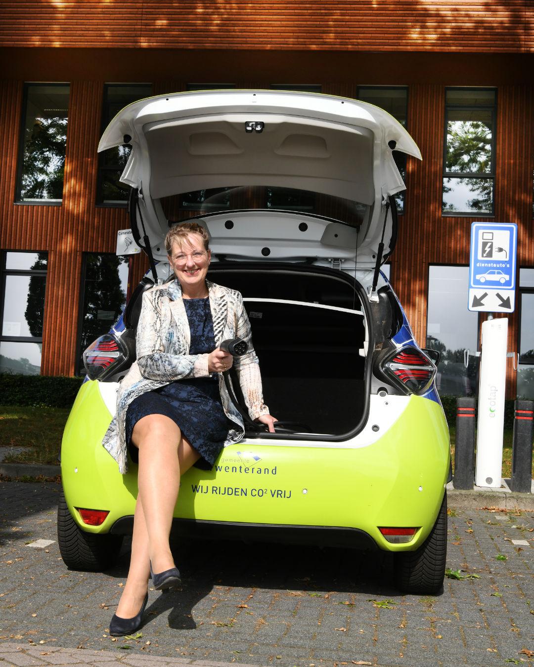 Wethouder Martha van Abbema bij de elektrische auto van Gemeente Twenterand