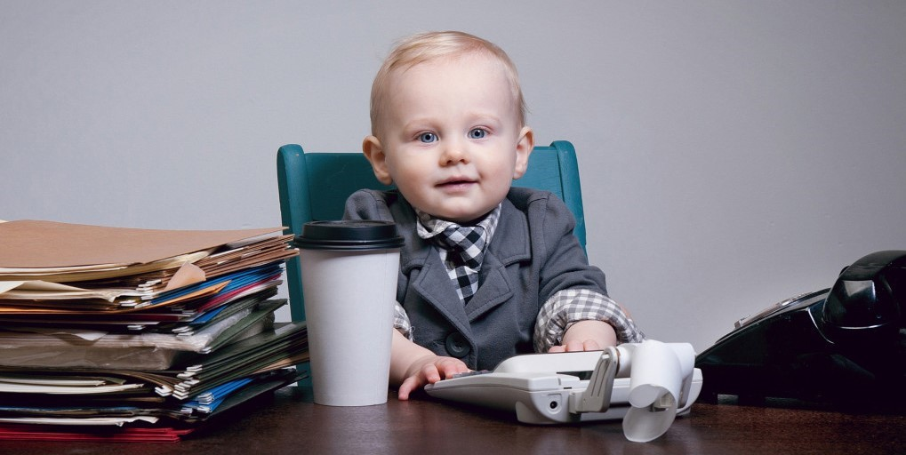 Picture of a baby in a buisness coat, sitting by a table