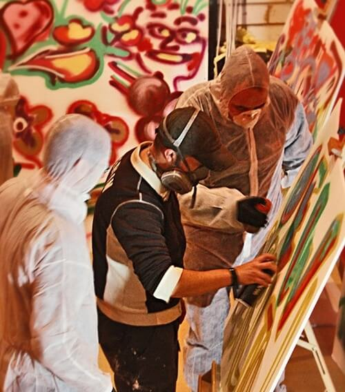 Teambuilding: Menschen sprühen zusammen Graffiti