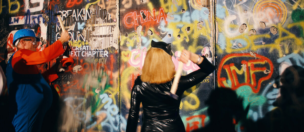 Zwei Personen schalgen mit Hammern an einer Graffiti Wand