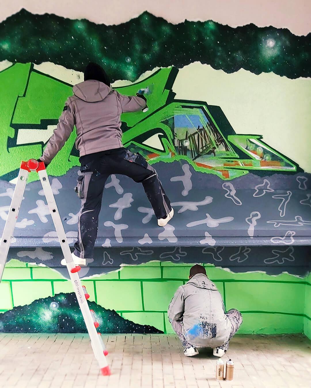 """Graffiti Hausdurchgang """"Stadt und Land"""" Berlin Hellersdorf Graffiti-Künstler mit Leiter bei der Arbeit"""