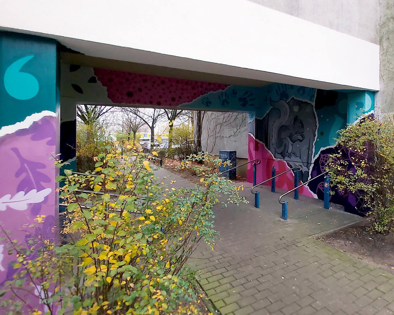 """Graffiti Hausdurchgang """"Stadt und Land"""" Berlin Hellersdorf pinker und türkiser Hausdurchgang mit Eichhörnchen"""
