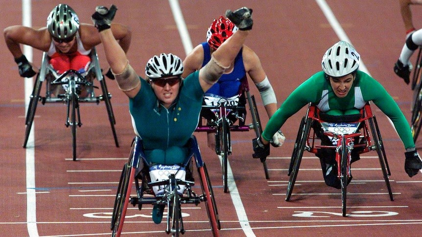 Louise Sauvage raises her hands over her head as she crossing the finish line
