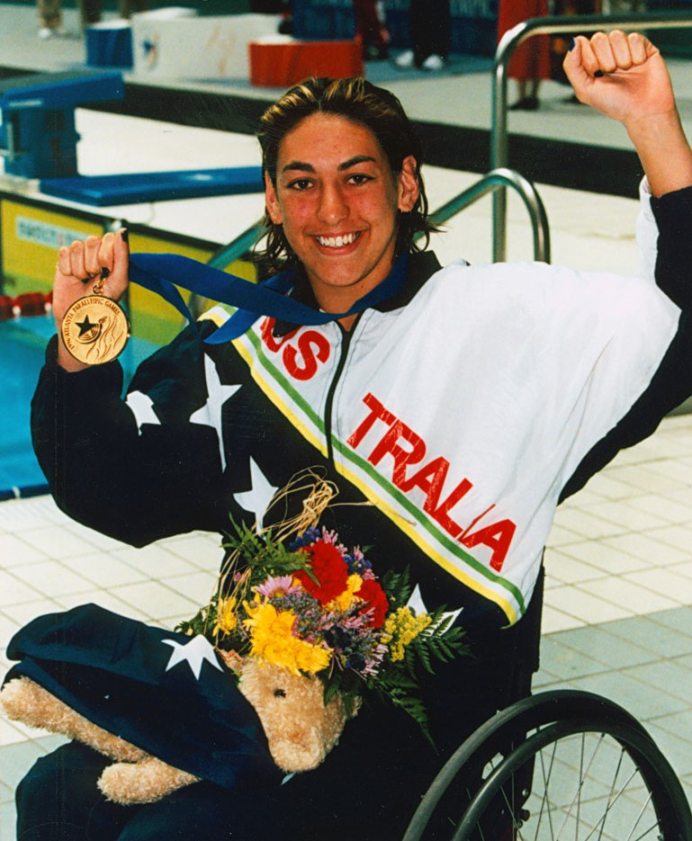 Priya Copper,  itting in a wheelchair, pumps her fist while holding her gold medal