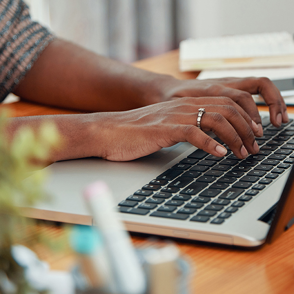 Hands typing on a laptop while seated at a desk.