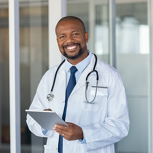 A physician smiles while he is writing on his clipboard.