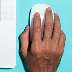 A hand clicks a white, wireless computer mouse.