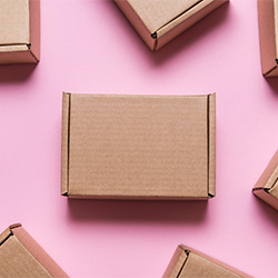 A plain shipping box surrounded by other boxes.