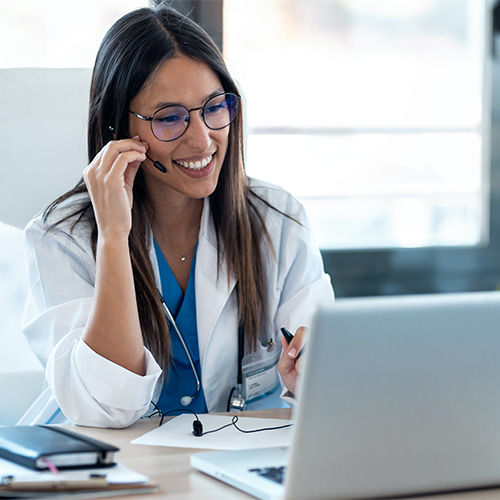 A female physician has a video chat on her laptop in her office.