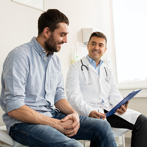 A doctor shows his patient something on a chart.