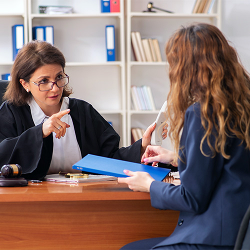 A female judge talks sternly to a plaintiff in her office.