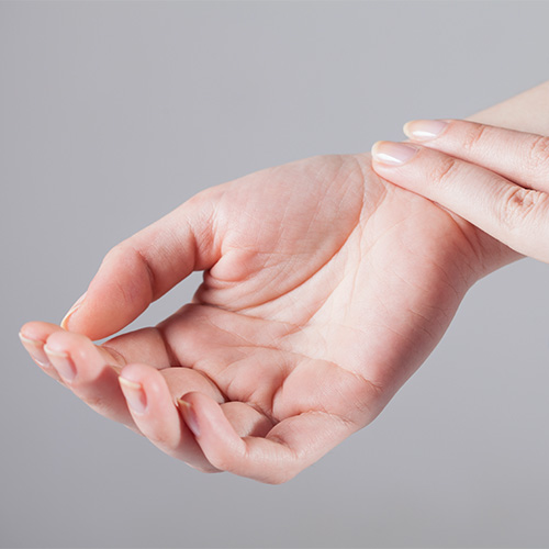 A person checking their pulse with two fingers on their wrist.