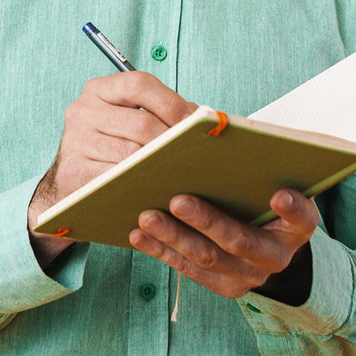 A worker writes metrics down on a clipboard.