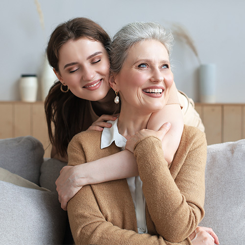 An older daughter hugging her mother and looking hopeful.