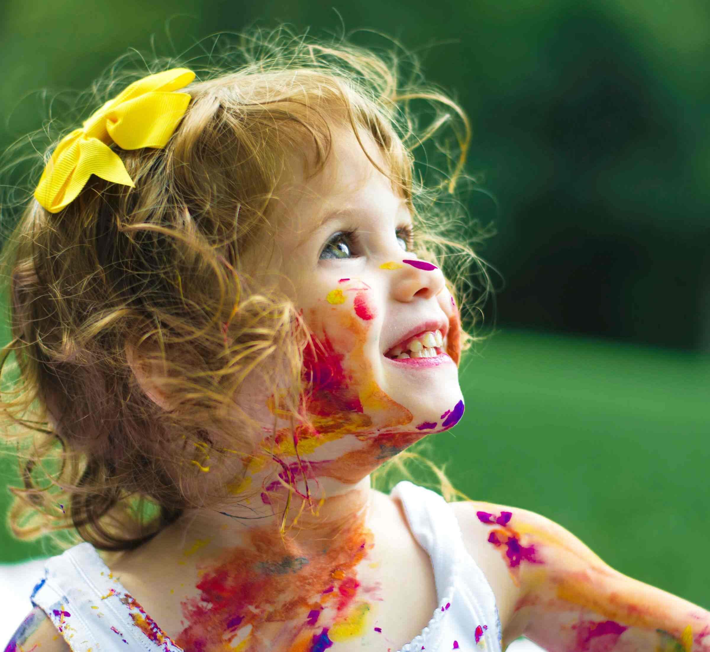 Lachendes Mädchen mit Farbe im Gesicht schaut nach oben (Foto von Senjuti Kundu auf Unsplash)