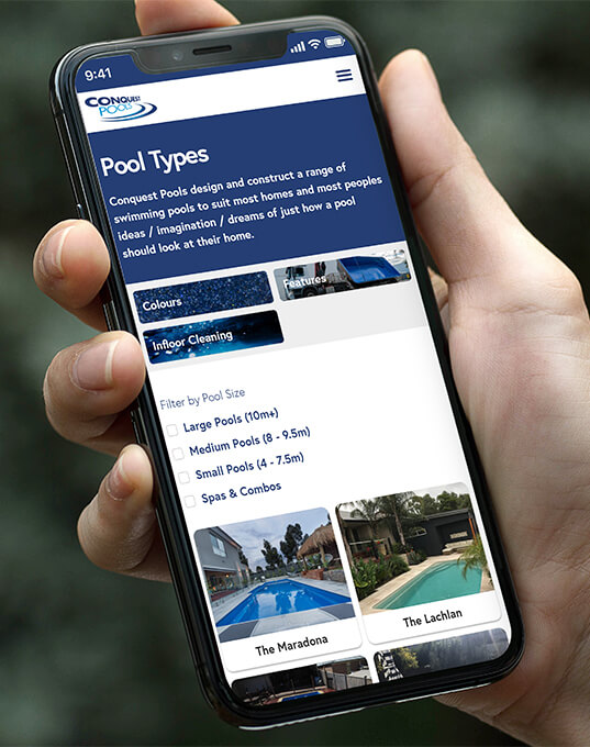 A hand holding a mobile phone showing the Conquest Pools pool page website