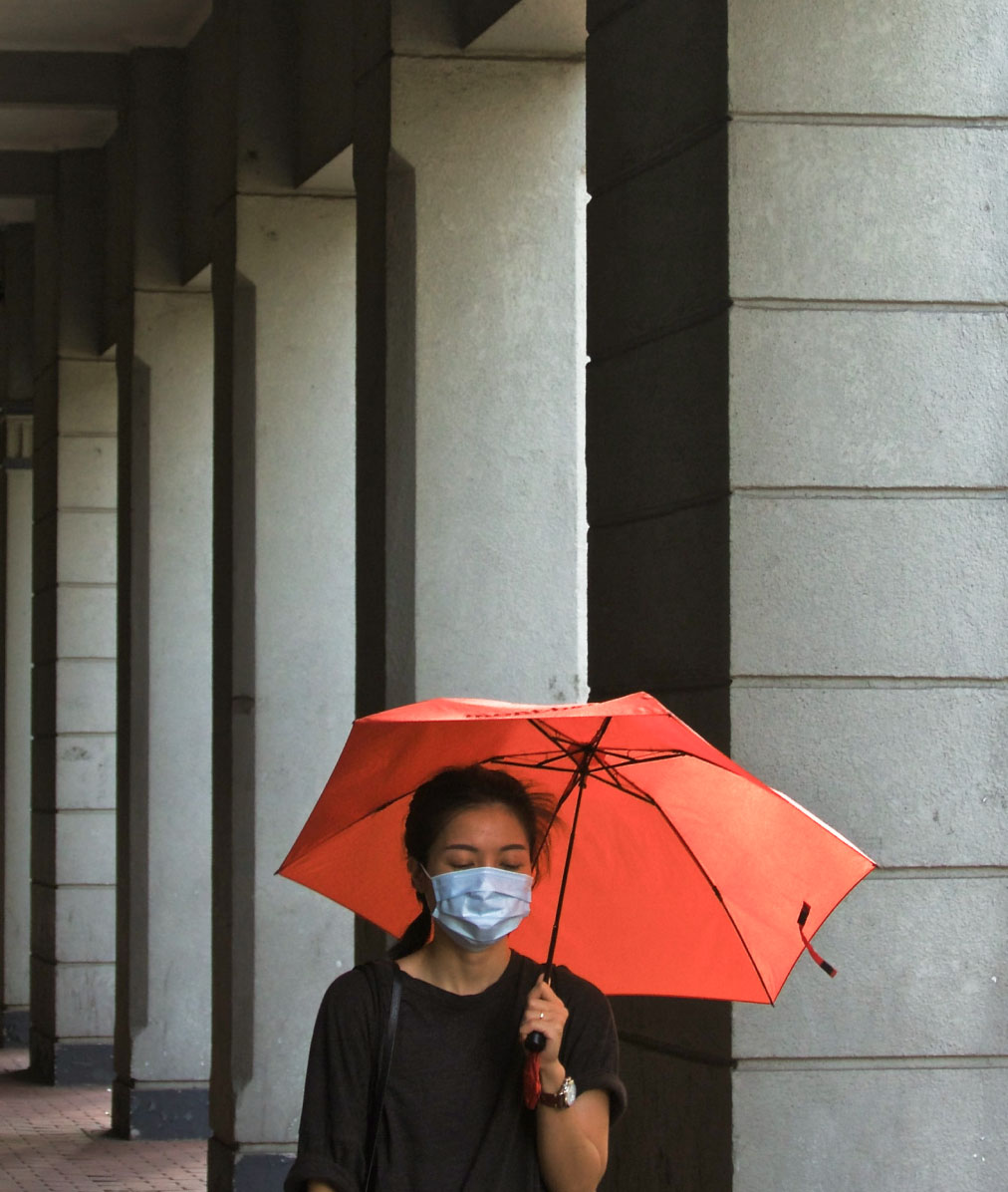Woman wearing a face mask holding an orange umbrella