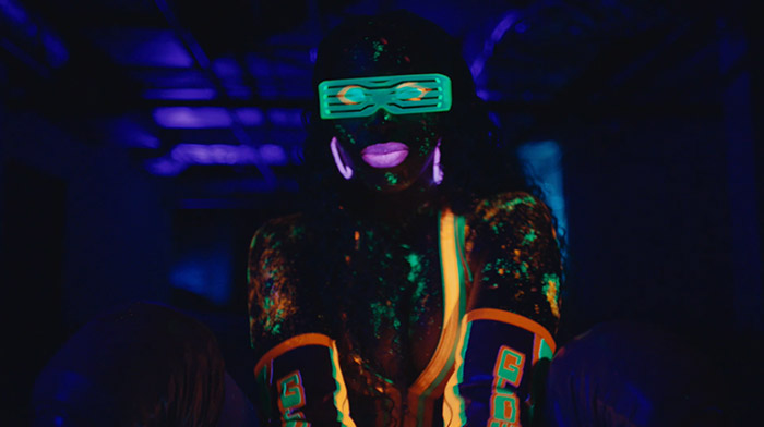 WWE commercial still of woman dancing with neon paint