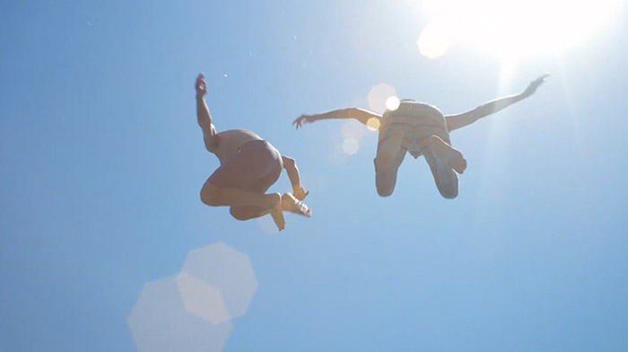 Corona commercial still of two friends jumping to the water