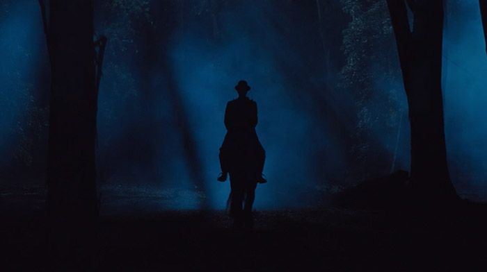Warsteiner commercial still of men with a hat ridding a horse in the woods during a foggy night
