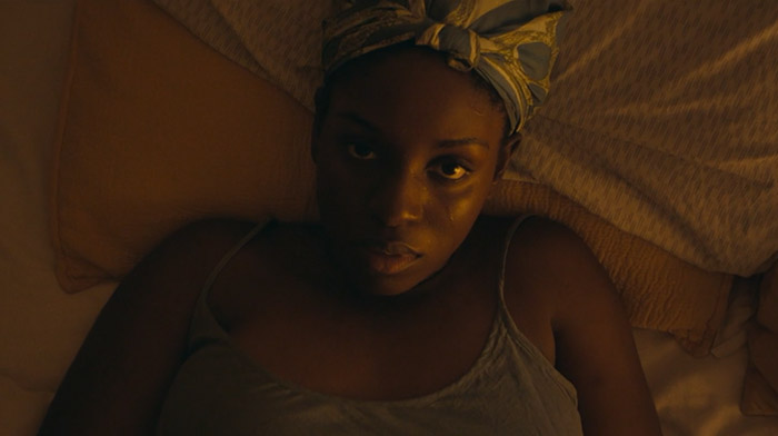 Further Away short film  still of a black young woman lying in bed looking straight into the camera