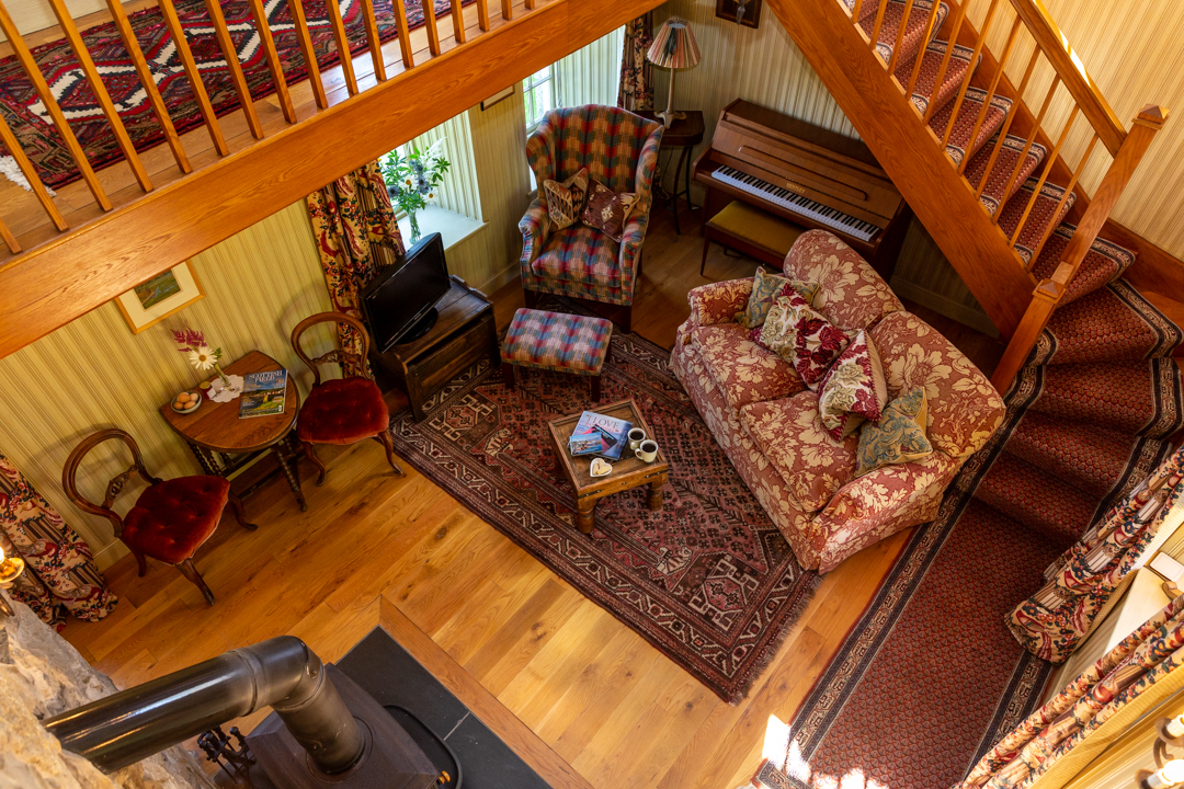 The warm and inviting living room of the Guardhouse cottage, with comfy sofas.
