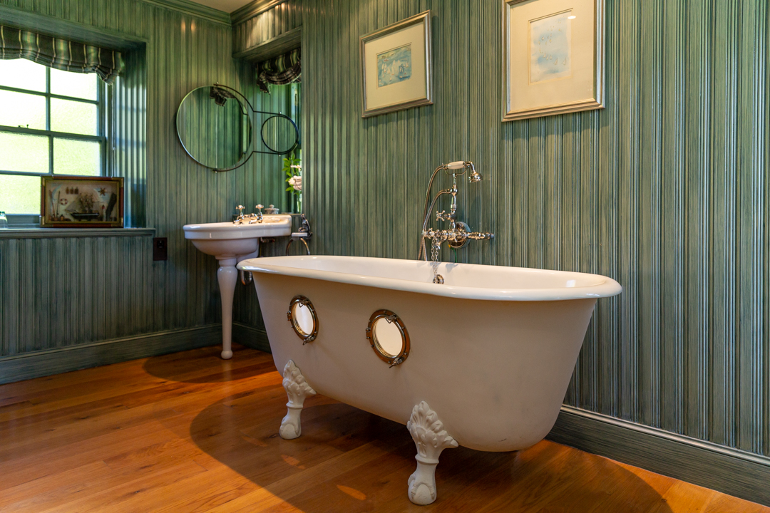 Large bathroom with roll-top bath with portholes.