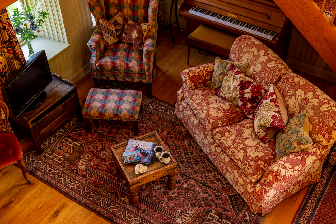 Warm and cosy living room with soft seating and piano