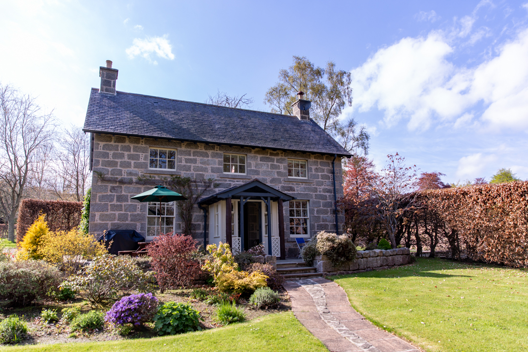 Picturesque cottage exterior with lush private garden and vines climbing the façade.