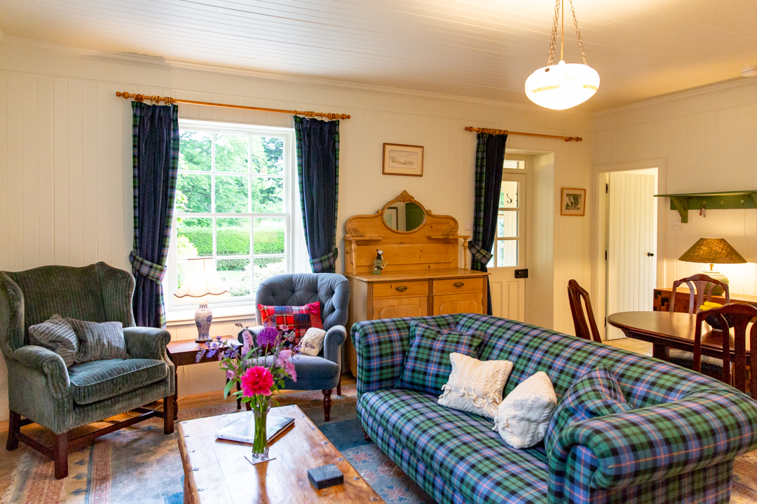 The sunny living room of the Pheasantry cottage with wood burning stove.